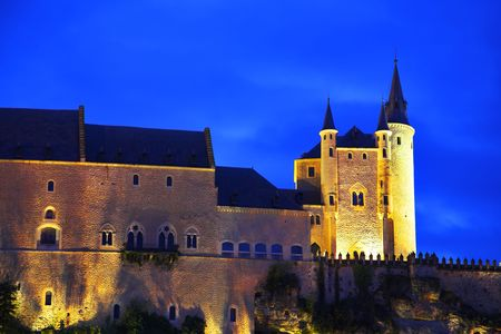 Palace of Spanish kings Alkasar in Segovia in twilight on a background of the cloudy sky photo