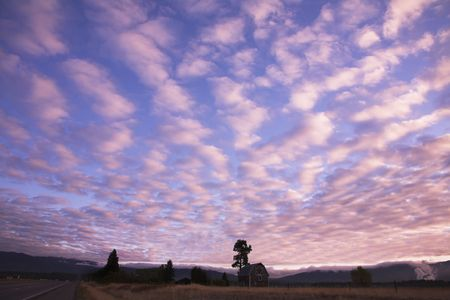 Pink clouds in the evening sky above the rural  near to road photo