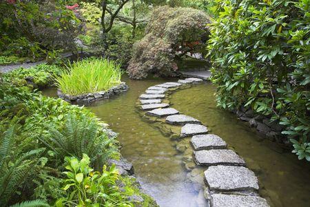 ponte giapponese: Un sentiero di pietre gettate con mattone attraverso una multa stagno in giardino giapponese