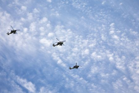 flight mode: Three fighting helicopters beautifully flying on military-air parade in the cloudy sky