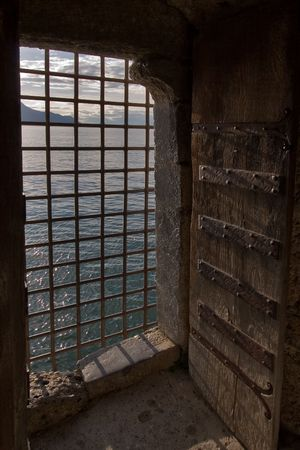 The big window aperture closed by a lattice in a fortress ?hillon on coast of lake Leman photo