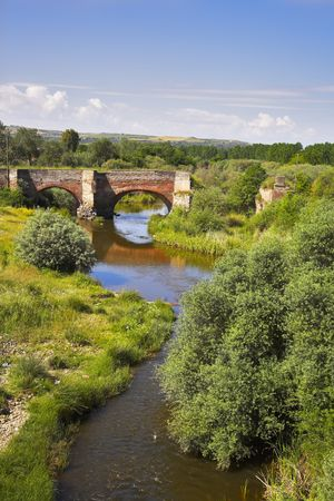The ancient bridge through a stream in the Spanish countryside photo