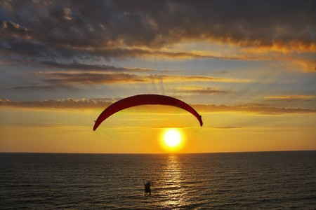 Flight on an operated parachute in twilight on a sunset. A magnificent parachute in the cloudy sky above the sea Stock Photo - 4037710