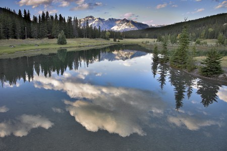 The sun shines tops of distant mountains, clouds above lake and fur-trees on coast photo