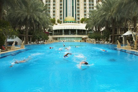 Group of fine sportsmen on training in pool of magnificent hotel photo