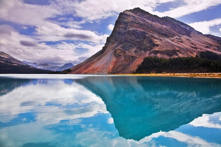The huge rock of the triangular form is reflected in emerald waters of cold mountain lake Stock Photo - 4437074