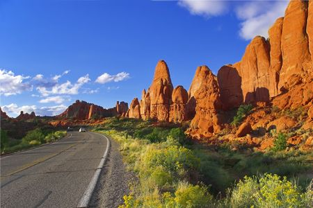 Road among freakish natural stone formations in the well-known park Arches in the USA  photo