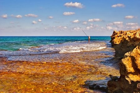 Lonely fisherman on a sunny sea shore Stock Photo - 4677330