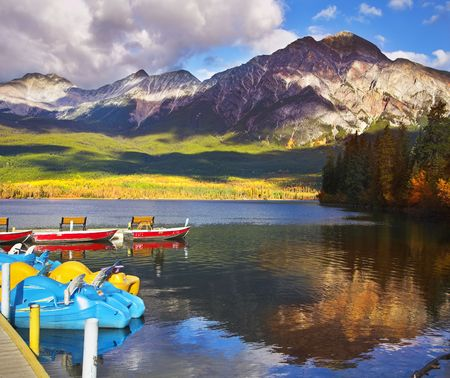 Magnificent morning on Pyramidal lake in Canada. A boat mooring and a dog photo