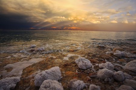 Coast of the Dead Sea in Israel in a spring thunder-storm. The coastal stones covered by salty adjournment Stock Photo - 4749240