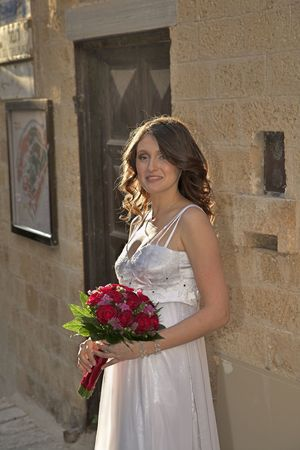 The beautiful bride with a wedding bouquet has thoughtfully leant against a wall of old city. Stock Photo