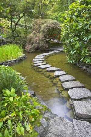 A footpath from stones laid with brick through a fine pond in Japanese garden photo
