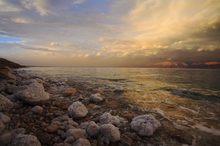 adjournment: Coast of the Dead Sea in Israel in a spring thunder-storm. The coastal stones covered by salty adjournment