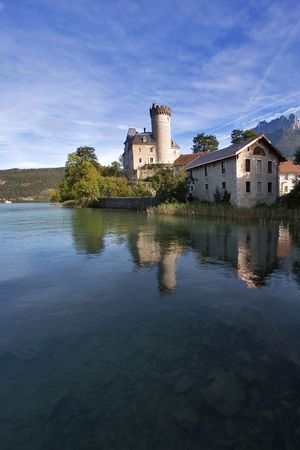 Middle-aged castle on a lake bank on a bright day