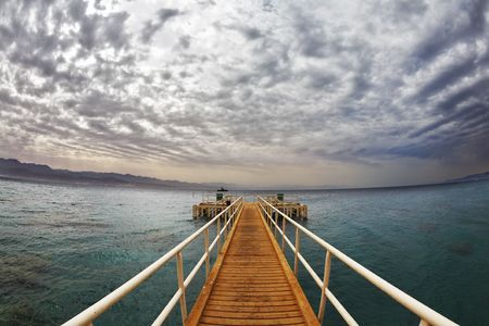 Wooden pier on a beach of Red sea in Eilat photo