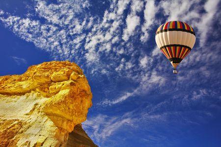 The bright decorative balloon flies above stone desert  Stock Photo - 5437356