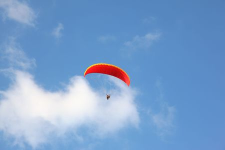 The operated red parachute flies in high in the blue sky Stock Photo - 5494608
