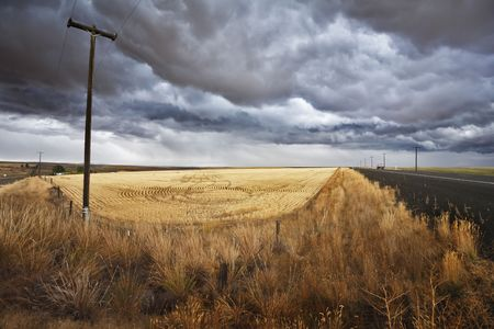 Soil rural road and columns of an electric main to fields of Montana. The thunder-storm begins photo