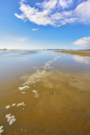 outflow: Wide sandy beach and sea foam on sand during outflow