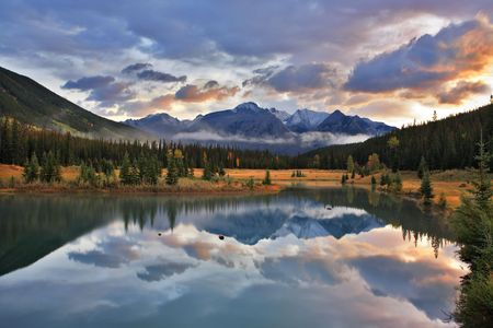 Dark blue cold lake, forest coast and snow mountains in Canada