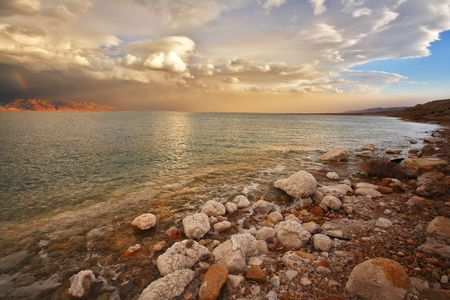 Coast of the Dead Sea in Israel in a spring thunder-storm. Coastal stones are covered by salt Stock Photo - 6161394