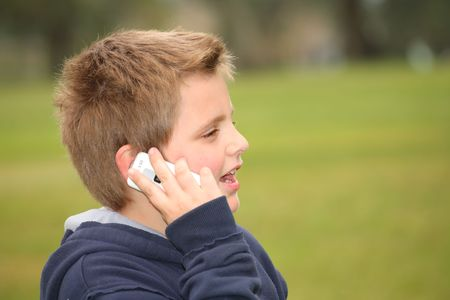 The beautiful European white boy in park talks on a cellular telephone Stock Photo - 6627229