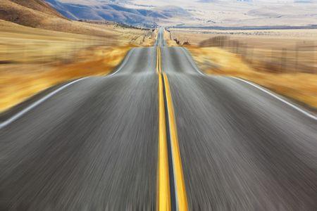 celerity:  Un espejismo en alta velocidad. Magn�fica carretera estadounidense y fencings en carreteras de derivas de nieve Foto de archivo