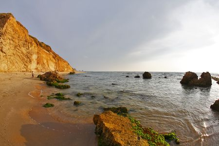 Wet green moss on huge stones of a beach on Mediterranean sea photo