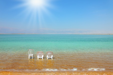 dead sea: White beach armchairs and a chair in the warm clear water beach. Beach at the Dead Sea,  sunny day in May