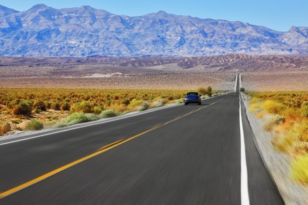 The blue car was going at high speed, crossing Death Valley in the USA. The low dry bushes and mountains