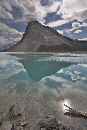 The huge rock of the triangular form is reflected in emerald waters of cold mountain lake Stock Photo - 7744717
