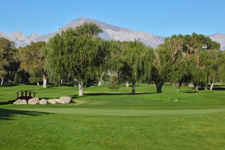 golf of california: The picturesque golf course in Bishop, California. Beautiful grassy lawn, large trees and a small bridge over a stream Stock Photo