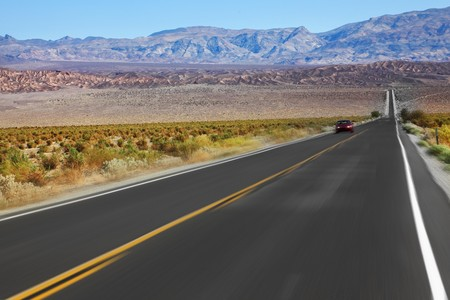 The red car was going at high speed, crossing Death Valley in the USA. The low dry bushes and mountains Banco de Imagens