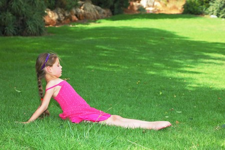 Lovely girl in pink dress shows gymnastics photo