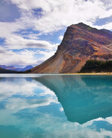 The huge rock is reflected in emerald waters of cold mountain lake Stock Photo - 8145925