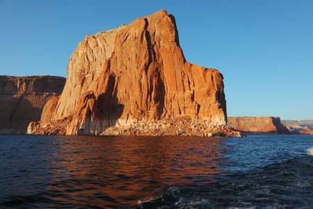 astern: Travel voyage by boat on Lake Powell. Picturesque waves astern the ship. Sunset rays illuminate the rocks on the shore of the lake. Arizona, USA.