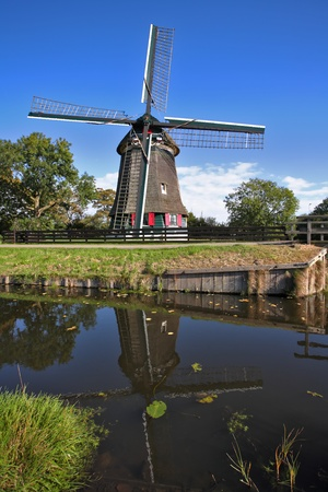 Ancient small village in Holland with windmills and the channel photo