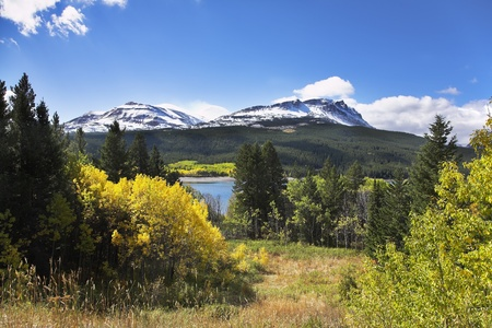 Classical northern landscape - cold lake, mountains with a snow and the turned yellow bushes