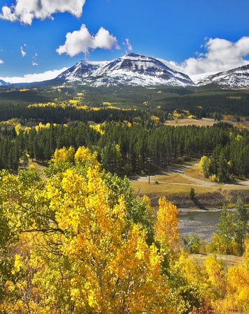 Rocky mountains, cold lake and charming green fur-trees Standard-Bild