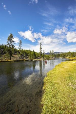 The fisherman in a red jacket with a fishing tackle will fish in the superficial small river Stock Photo - 8512736