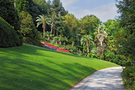 The flowerbeds, green grassy lawn and comfortable path in an exotic park. Lake Como, Villa Carlotta  photo