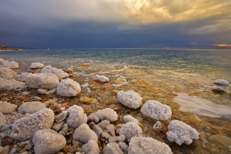 Coast of the Dead Sea in Israel in a spring thunder-storm. Coastal stones are covered by salt photo