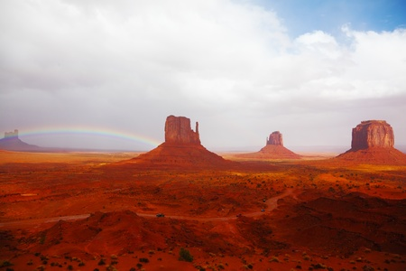 Famous mittens of red sandstone in a fog after the storm and a rainbow in the sky photo