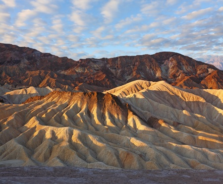 Sunset. The famous section of Death Valley in California - Zabriskie Point. Picturesque hills of pink, yellow and chocolate hues photo