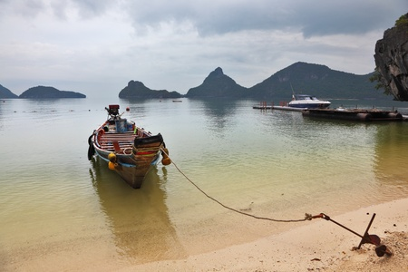 Thai Longtal boat moored on a sandy beach with an anchor. Picturesque bay on the island surrounded by islands Stock Photo - 9635656