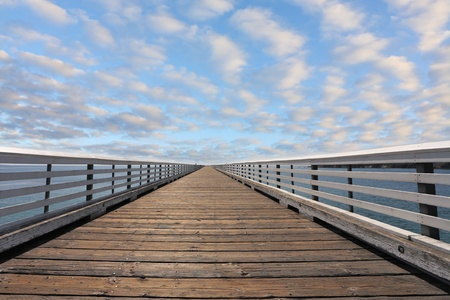 Wooden pier with a handrail. Pacific coast of California, the USA. Solar serene autumn day, the blue sky and easy clouds Standard-Bild