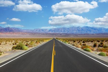 Grande strada americana, che attraversa un'enorme valle della morte in California. Un viaggio all'alta velocità Archivio Fotografico - 9850778