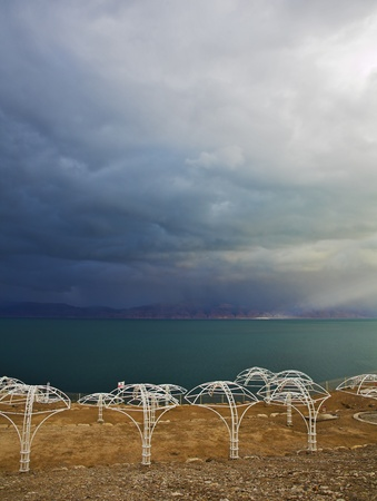 A beach canopies on deserted coast of the Dead Sea in a thunder-storm photo