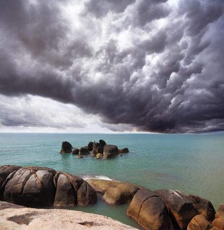 Storm cloud over the southern sea. Coastal rocks shine under the sunset sun photo