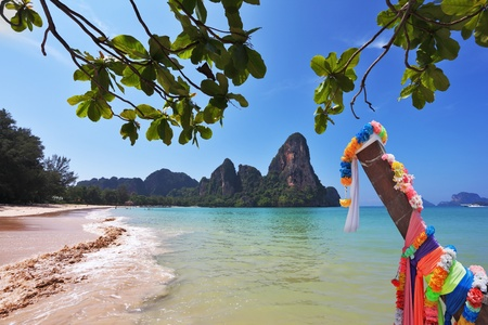Beautifully decorated with colored silks Native boat Longtail on a sandy beach in Thailand photo